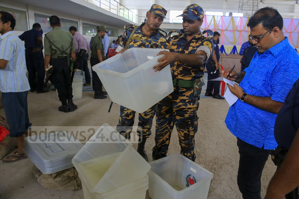 Security forces and election officials test ballot boxes. Photo: Mostafigur Rahman