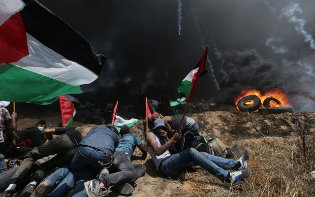Palestinian demonstrators take cover from Israeli fire and tear gas during a protest against US embassy move to Jerusalem and ahead of the 70th anniversary of Nakba, at the Israel-Gaza border in the southern Gaza Strip May 14, 2018. Reuters