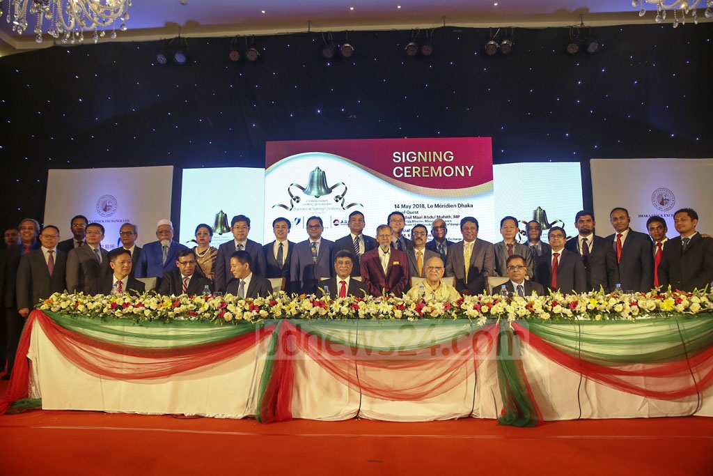 Officials pose for photograph after the signing of an agreement between Dhaka Stock Exchange and a consortium of China's Shenzhen and Shanghai bourses on strategic partnership at a hotel in the capital on Monday.