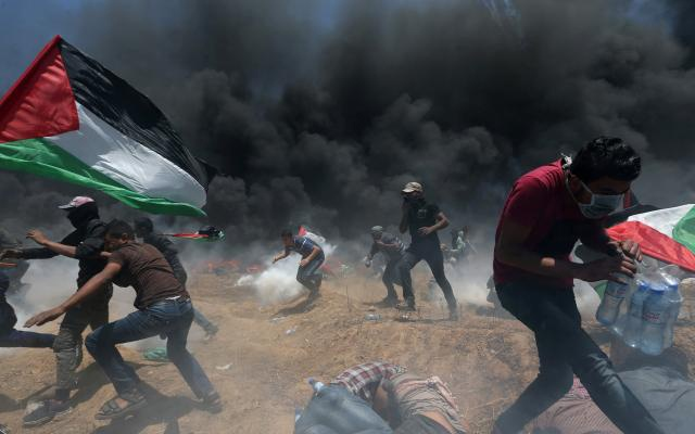 Palestinian demonstrators run for cover from Israeli fire and tear gas during a protest against US