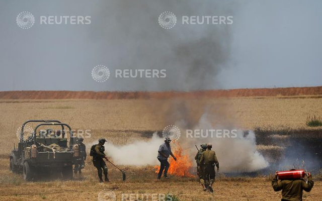 Israeli soldiers attempt to extinguish a fire in a field on the Israeli side of the border fence between Israel and Gaza near kibbutz Mefalsim, Israel, May 14, 2018. REUTERS/Amir Cohen