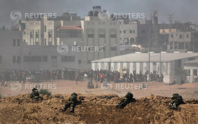 Smoke rises as Israeli soldiers are seen on the Israeli side of the border with the Gaza Strip, Israel, May 14, 2018. REUTERS/Amir Cohen