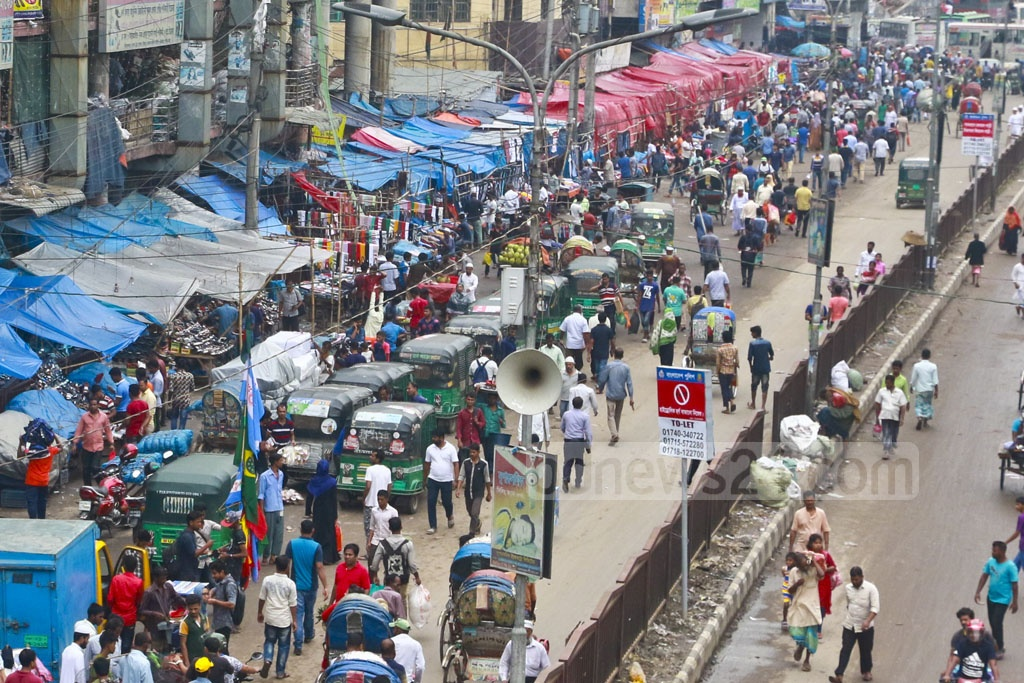 Pedestrians walk on the street as the pavements have been gobbled up by hawkers. This photo shows Gulistan-Fulbaria area on Wednesday. Photo: Abdullah Al Momin