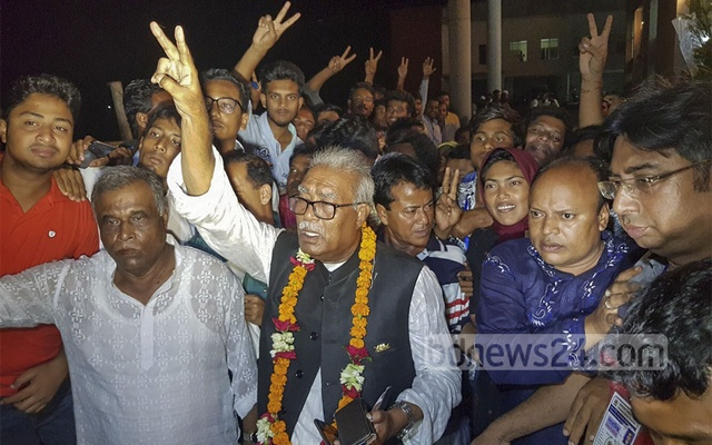 Awami League's Talukdar Abdul Khalek flashes the victory sign as initial results suggest he has won back the mayor's post in Tuesday's election to Khulna City Corporation.