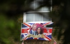 A Union Flag decorated with images of Prince Harry and Meghan Markle hangs from a building outside Windsor Castle ahead of their wedding, in Windsor, Britain May 16, 2018. Reuters