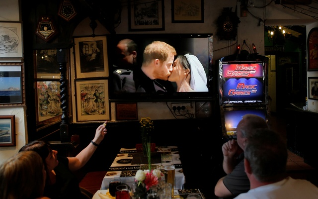 British tourists watch as Britain's Prince Harry and Meghan Markle kiss on the steps of St George's Chapel in Windsor Castle after their wedding, on a television in a restaurant in the British overseas territory of Gibraltar, historically claimed by Spain May 19, 2018. REUTERS/Jon Nazca