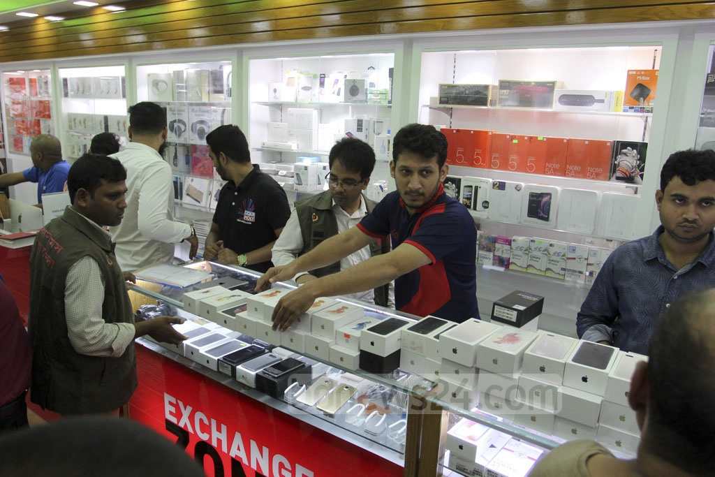 Customs intelligence officials hunt for illegally imported mobile handsets at a shop in the Bashundhara City Shopping Mall in Dhaka on Saturday. Photo: Asif Mahmud Ove