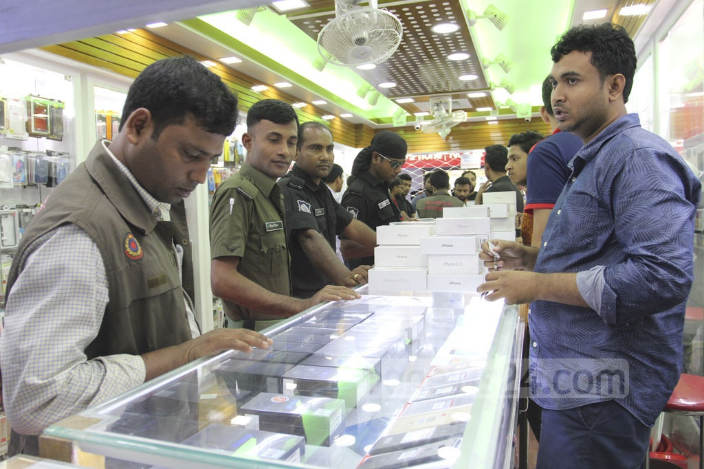 Customs intelligence officials conduct a drive against illegally imported mobile handsets at the Bashundhara City Shopping Mall in Dhaka on Saturday. Photo: Asif Mahmud Ove