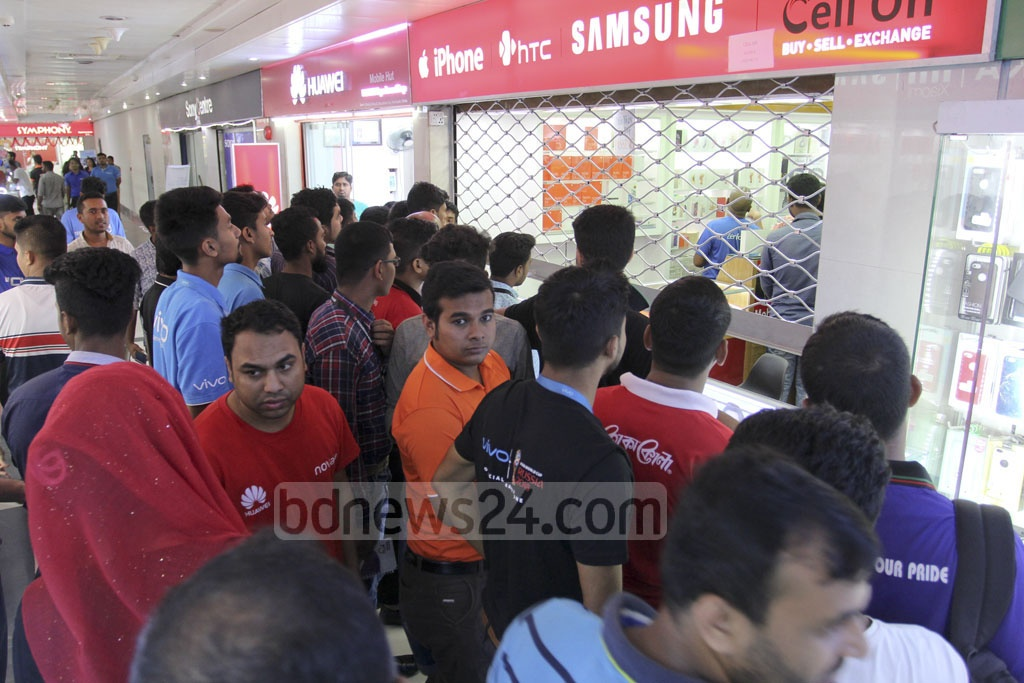 Crowds gather during an operation conducted by customs intelligence officials against sales of illegally imported mobile handsets at a shop in the Bashundhara City Shopping Mall in Dhaka on Saturday. Photo: Asif Mahmud Ove
