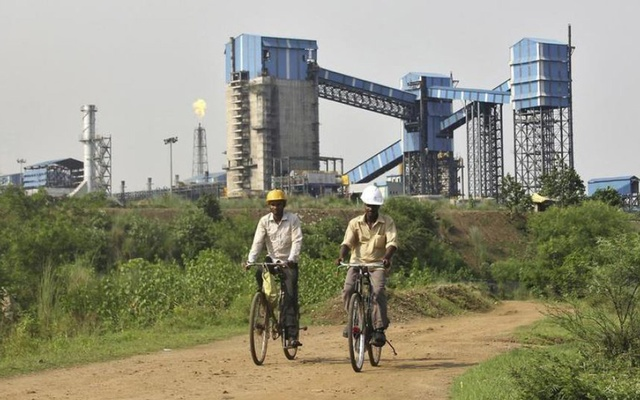 File Photo: Men ride their bicycles in front of the Bhushan Steel plant in the eastern Indian state of Odisha August 18, 2014. Reuters