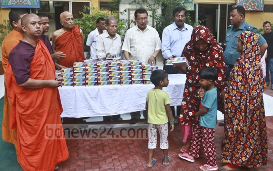 Buddhist monks distributing Iftar items among poor Muslims at a monastery in Dhaka's Basabo on Wednesday.