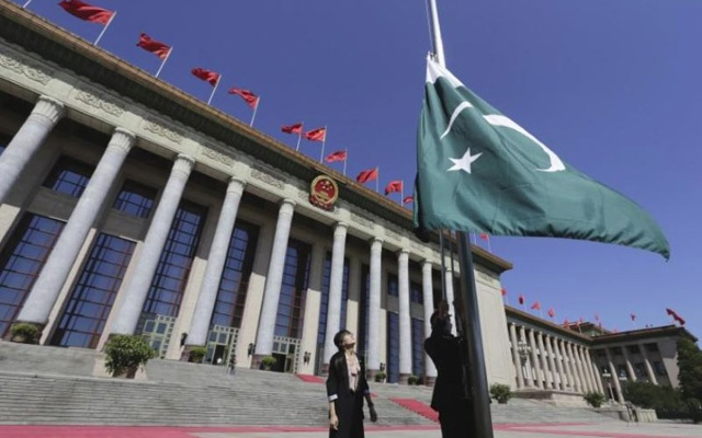 FILE PHOTO: A staff member raises Pakistan's flag in front of the Great Hall of the People ahead of a welcome ceremony for Pakistan's Prime Minister in Beijing, July 5, 2013. Reuters