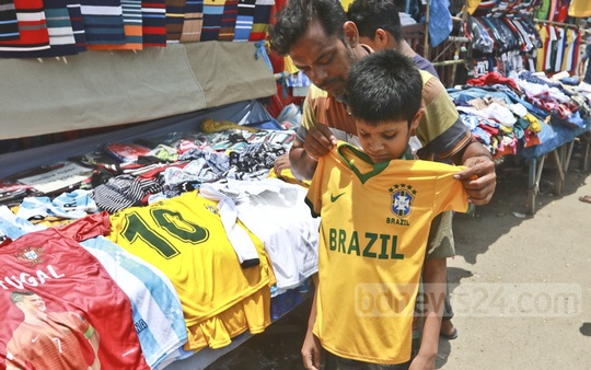 A child checks the size of a football jersey at a roadside stand in Dhaka's Gulistan. Photo: Abdullah Al Momin