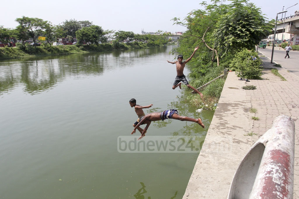 Children frolic in the waters of the Kuril Flyover Lake. The picture was taken on Tuesday. Photo: Asif Mahmud Ove
