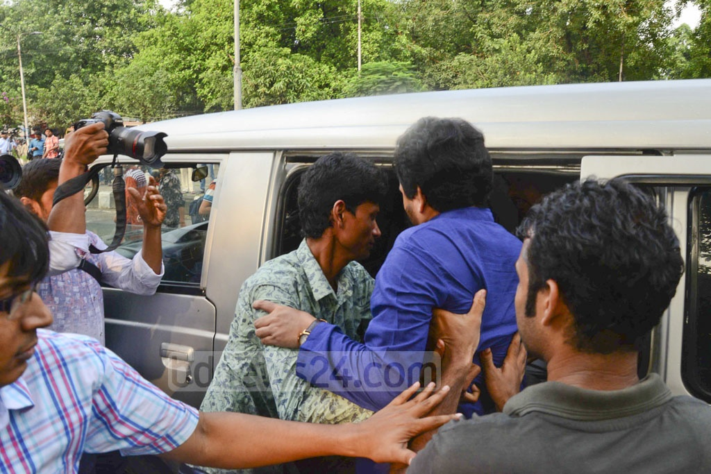 RAB personnel escorting Ganajagaran Mancha Spokesperson Imran H Sarker to a car as he was detained from a protest rally against 'extrajudicial killings' during anti-drug operations at Shahbagh on Wednesday.