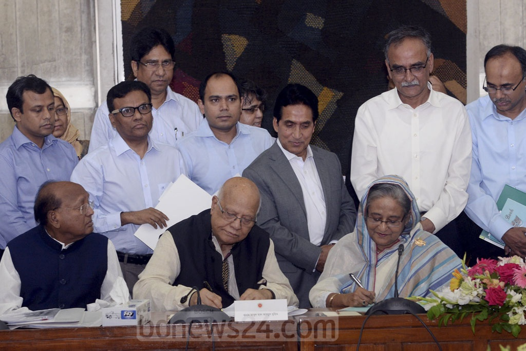 Prime Minister Sheikh Hasina and Finance Minister AMA Muhith sign the approved national budget at a cabinet meeting prior to its presentation in parliament on Thursday. Photo: PID