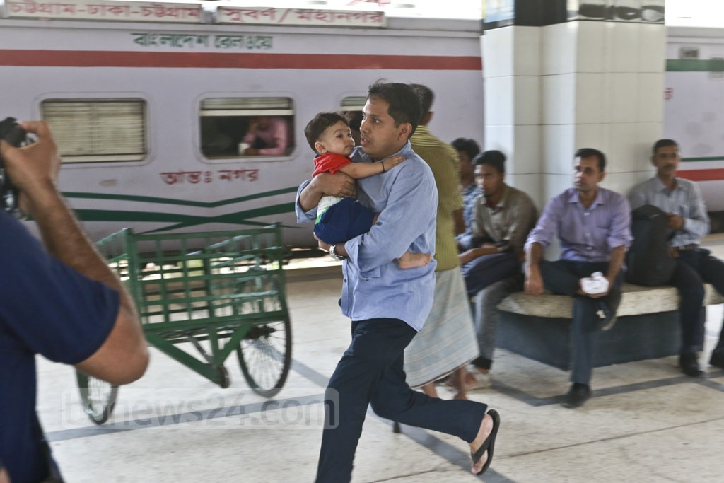 A man with his child in his arms makes a desperate dash to catch the train. Photo: Abdullah Al Momin