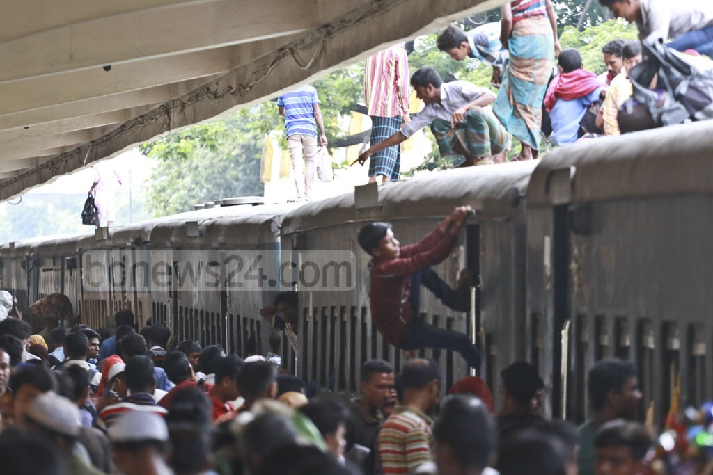 Homebound people scrambling to climb onto the roof of an overcrowded train at Kamalapur Railway Station on Sunday, risking their lives as they leave for home ahead of Eid. Photo: Abdullah Al Momin