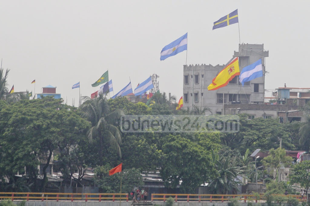 The flags of various countries competing in the FIFA World Cup fly atop the roofs of homes in Dhaka's Aminbazar. Photo: Asif Mahmud Ove