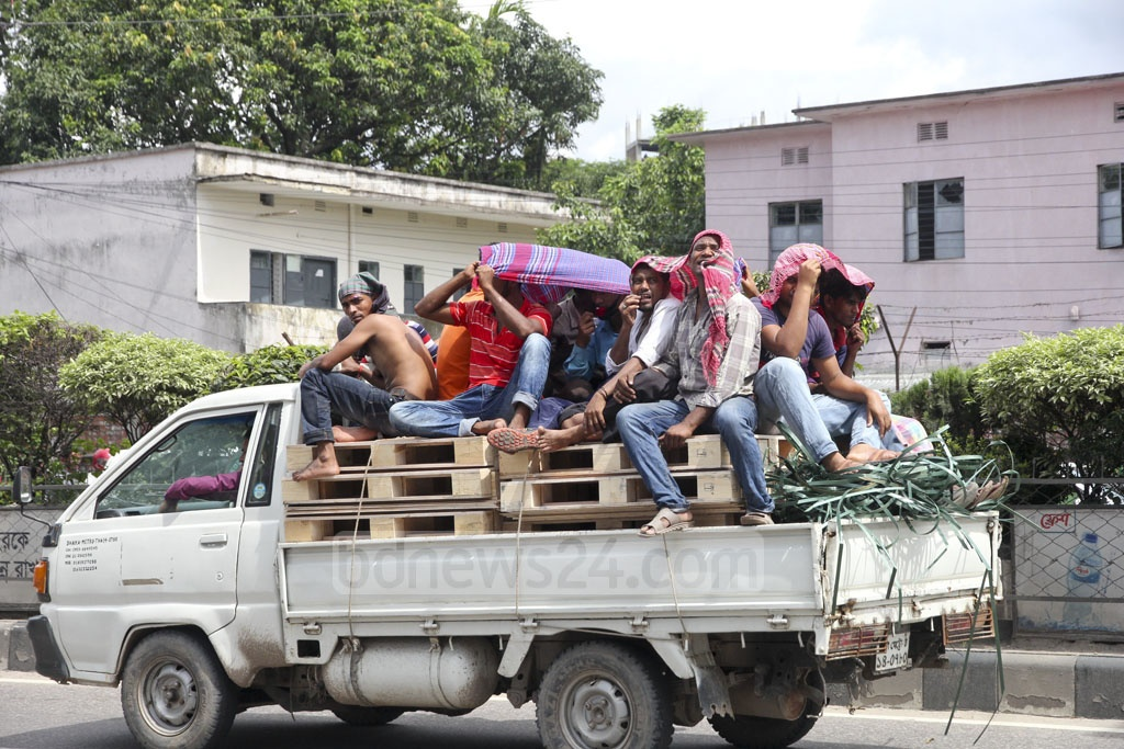 Workers on the back of a pickup van cover their heads with cloth to ward off the simmering heat. Photo: Asif Mahmud Ove