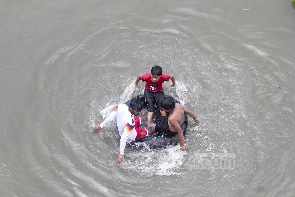 A group of three floats atop a tube in an attempt to ward off the heat in Gabtoli. Photo: Asif Mahmud Ove