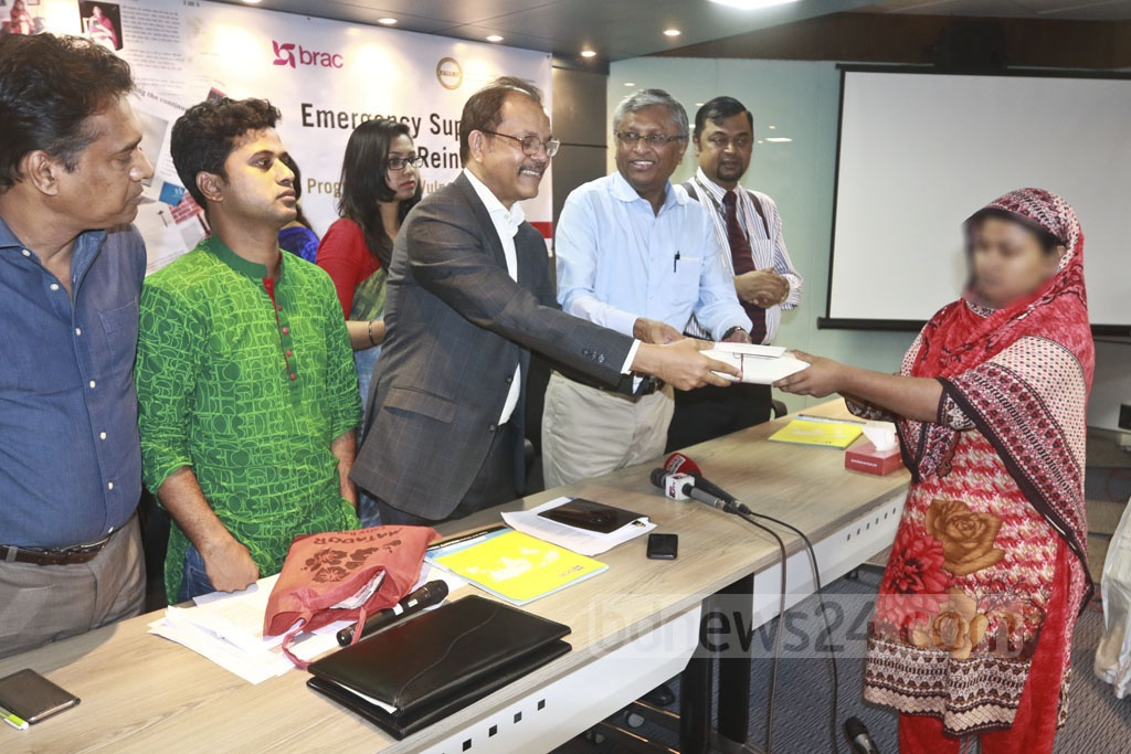 National Human Rights Commission Chairman Kazi Reazul Hoque hands cheques over to 22 women workers who returned home from abroad. The event was organised by BRAC and the Leathergoods and Footwear Manufacturers & Exporters Association of Bangladesh on Monday. Photo: Abdullah Al Momin