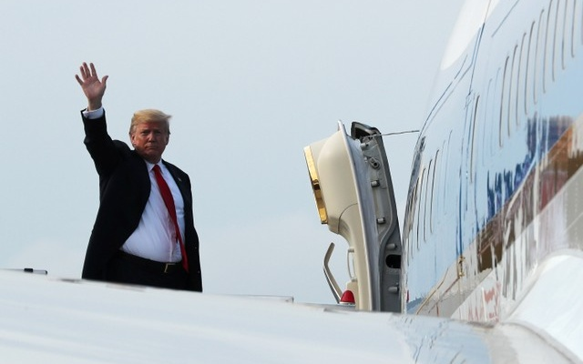 US President Donald Trump waves as he boards Air Force One after his summit with North Korean leader Kim Jong Un in Singapore June 12, 2018. Reuters