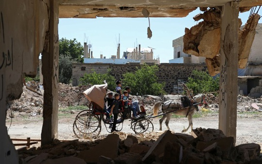 Children ride a horse cart past a damaged house on the first day of the Muslim holiday of Eid al-Fitr, in the rebel-held town of Dael, Syria June 15, 2018. REUTERS/Alaa Al-Faqir