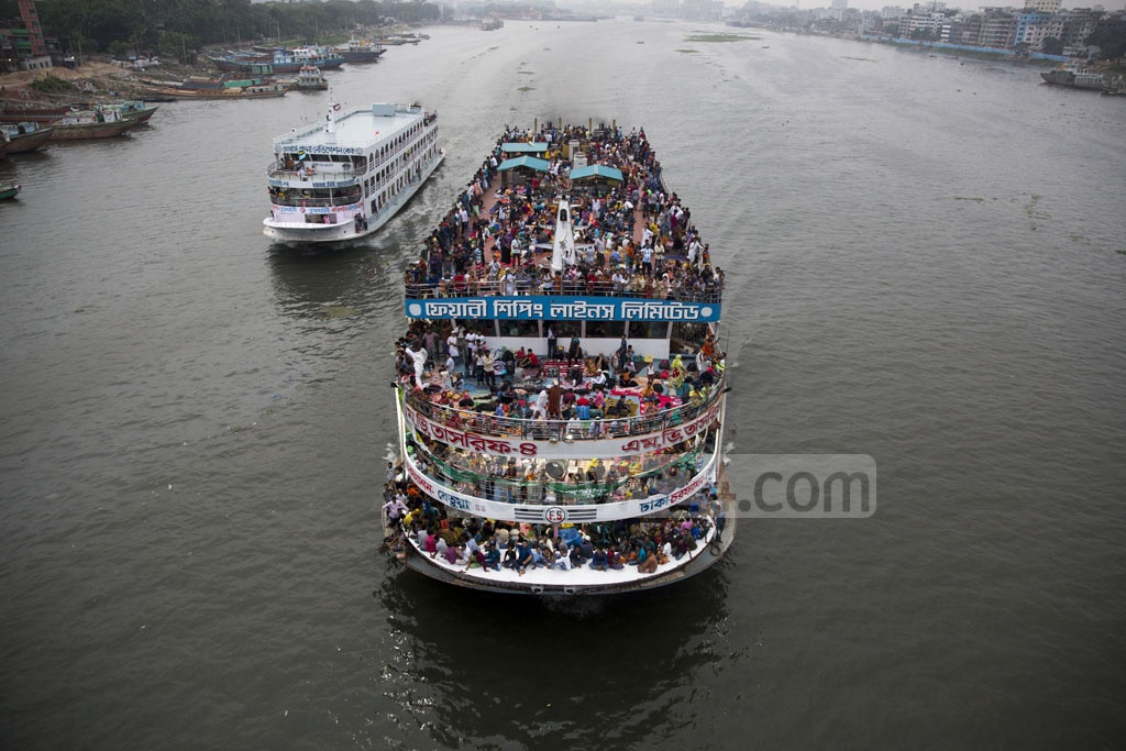 Many of the Eid holidaymakers risk their lives and those of other passengers by taking rides on the roofs of launches. This photo was taken from the China-Bangladesh Frienship Bridge on the Burhiganga River at Postogola on Friday. Photo: Mostafigur Rahman