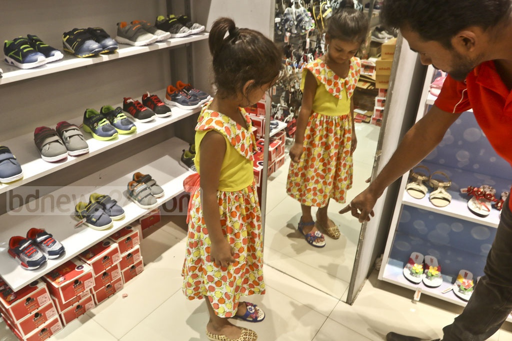 A child chooses a pair of shoes for Eid shopping at Dhaka's Elephant Road. Photo: Abdullah Al Momin