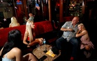 Dennis Hof, a legal brothel owner and recent winner of the Republican primary election for Nevada State Assembly District 36, sits in the parlour with Misty Matrix (R) his girlfriend and a legal prostitute, and other working girls at his Moonlite BunnyRanch legal brothel n Mound House, Nevada, US Jun 16, 2018. Reuters