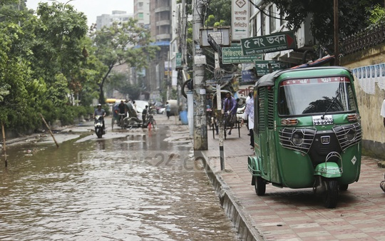 Autorickshaws and rickshaws have begun using the sidewalks to cross this waterlogged road in Dhaka's Shajahanpur. Photo: Mahmud Zaman Ovi