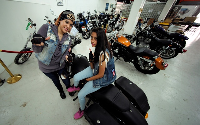 Saudi Doaa Bassem and Hanan Iskandar give thumbs up as they sit on a motorbike prior to their advance riding session at Harley Davidson dealer in Al Khobar