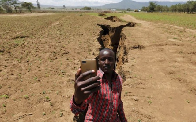 A man takes a selfie photograph near a chasm suspected to have been caused by a heavy downpour along an underground fault-line near the Rift Valley town of Mai Mahiu, Kenya March 28, 2018. Reuter
