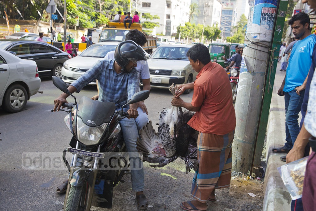 Two motorcycle passengers haggle with poultry traders over the price of a turkey at Dhaka's Gulshan-1 intersection on Sunday. Photo: Mostafigur Rahman