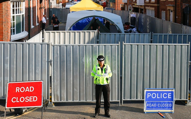 A police officer stands in front of screening erected behind John Baker House, after it was confirmed that two people had been poisoned with the nerve-agent Novichok, in Amesbury, Britain, Jul 5, 2018. Reuters