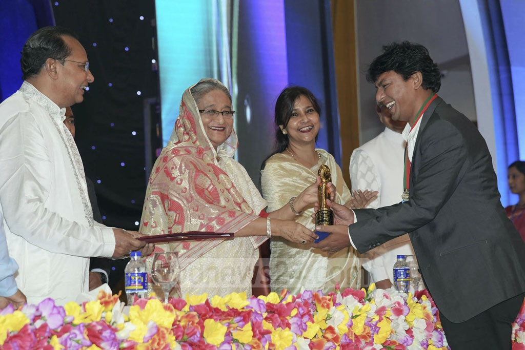 Chanchal Chowdhury receives the Best Actor award from Prime Minister Sheikh Hasina for his starring role in 'Aynabaji'.