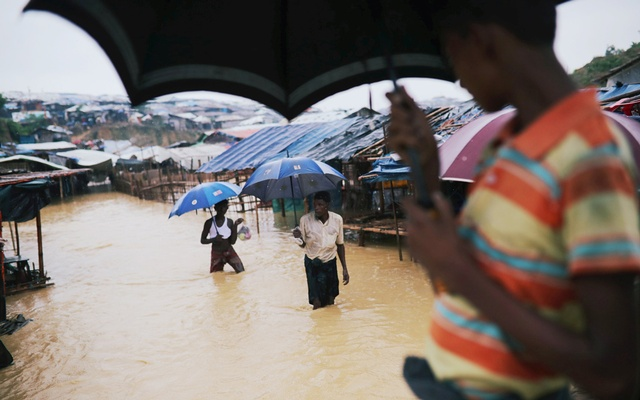 Rohingya refugee children walk along the water as parts of the Kutupalong camp flooded during heavy rain in Cox's Bazar, Bangladesh, Jul 4, 2018. Reuters