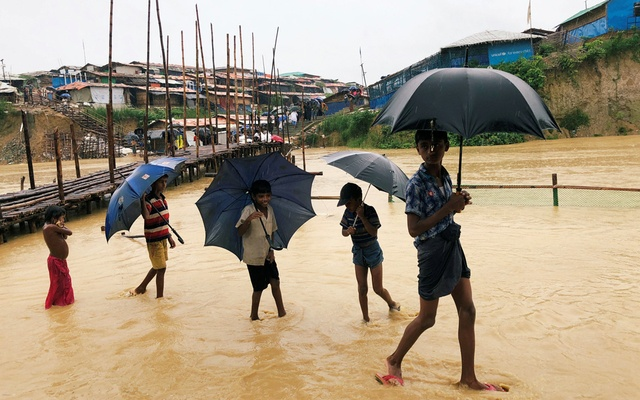 Rohingya refugee man with child returns to his shelter in Kutupalong camp during heavy rain in Cox's Bazar, Bangladesh, Jul 4, 2018. Reuters