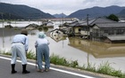 An elderly couple looks at a flooded area after heavy rain in Kurashiki, Okayama Prefecture, Japan, in this photo taken by Kyodo Jul 8, 2018. Kyodo via Reuters
