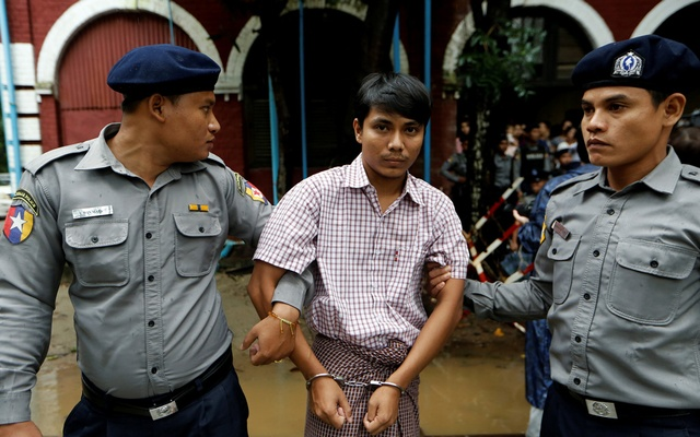 Detained Reuters journalist Kyaw Soe Oo is escorted by police while leaving Insein court in Yangon, Myanmar Jul 9, 2018. Reuters
