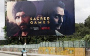 A man rides his scooter past a hoardings of Netflix's new television series