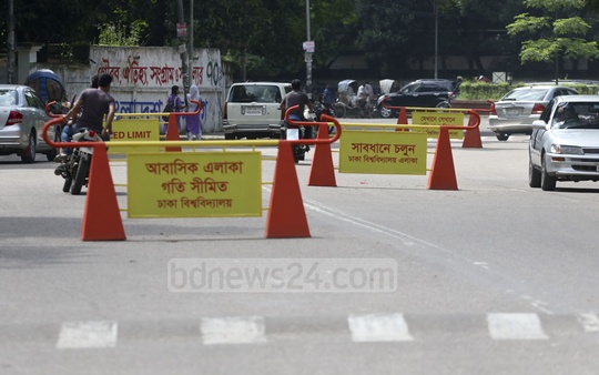 Barriers with safe driving messages have been set up on the Dhaka University road in order to control traffic. Photo: Abdullah Al Momin