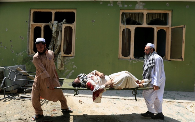 Men carry the body of a victim after an attack in Jalalabad city, Afghanistan July 11, 2018. REUTERS