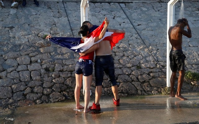 France fans celebrate under beach showers in Nice after they defeated Croatia in their Soccer World Cup final match.