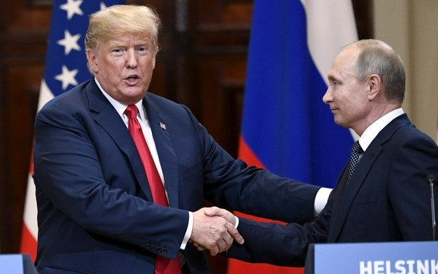 US President Donald Trump and Russia's President Vladimir Putin shake hands after their joint news conference in the Presidential Palace in Helsinki Finland