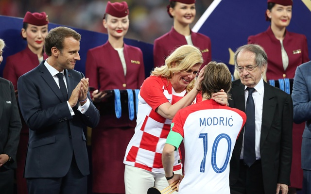 Croatia President Kolinda Grabar-Kitarovic speaks with Croatia's Luka Modric while President of France Emmanuel Macron looks on during the presentation. Reuters