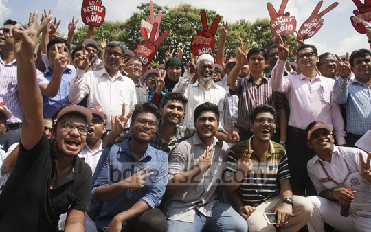 Teachers and students flash victory sign after publication of HSC exam results at Residential Model College in Dhaka on Thursday.
