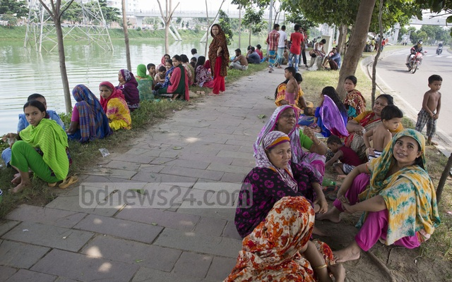 File Photo: Residents of Tejgaon's Kuniparha in Dhaka take rest under trees along the Hatirjheel lake during a power cut on July 19, the hottest day of the capital in 2018. Photo: Mostafigur Rahman