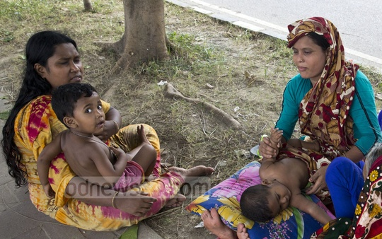 Residents of Tejgaon's Kuniparha in Dhaka take rest under trees along the Hatirjheel lake during a power cut on Thursday, the hottest day of the capital this year. Photo: Mostafigur Rahman